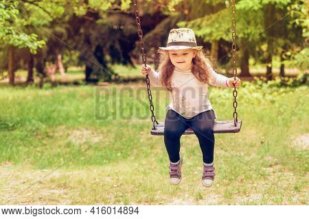 Child Playing In The Open Playground, Little Happy Laughing Girl Swinging On A Swing.