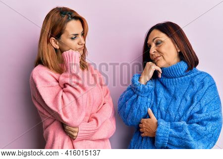 Latin mother and daughter wearing casual clothes thinking concentrated about doubt with finger on chin and looking up wondering