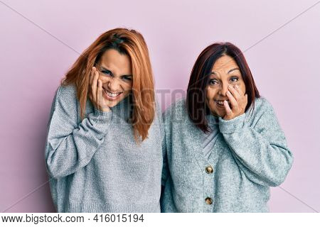 Latin mother and daughter wearing casual clothes laughing and embarrassed giggle covering mouth with hands, gossip and scandal concept