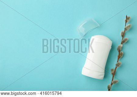 White Deodorant With Willow Twigs On Blue Background. Top View.