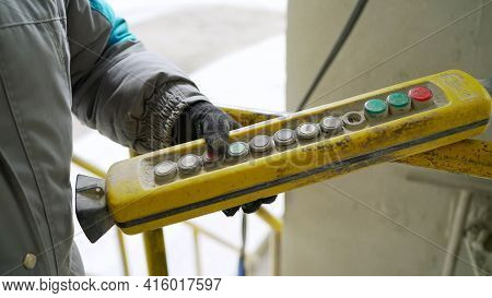 Male Hand Push Remote Control Switch For Overhead Crane In The Factory, Close-up. Electrical Control