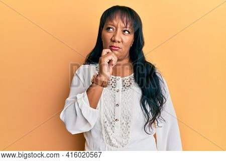 Middle age african american woman wearing casual clothes thinking concentrated about doubt with finger on chin and looking up wondering