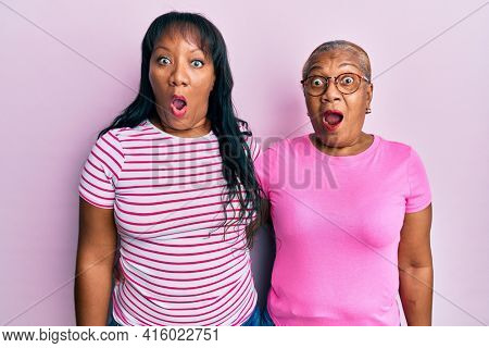 Hispanic family of mother and daughter hugging together with love scared and amazed with open mouth for surprise, disbelief face