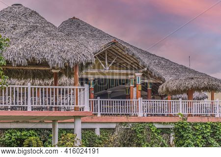 Cosy Straw Roofed Bungalows At Sunset At A Beach Resort In Cuba
