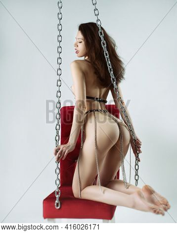 A Naked Woman In Leather Belts And Bdsm Accessories Chains On A Red Chair With A White Background Po