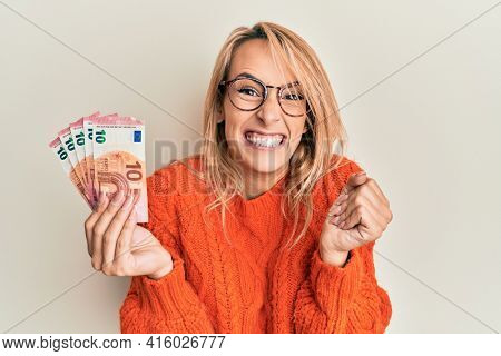 Beautiful blonde woman holding 10 euro banknotes screaming proud, celebrating victory and success very excited with raised arm