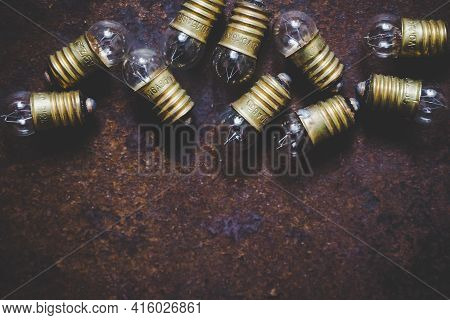 Incandescent Glass Light Bulbs On Rough Metal Surface, Top View, Background