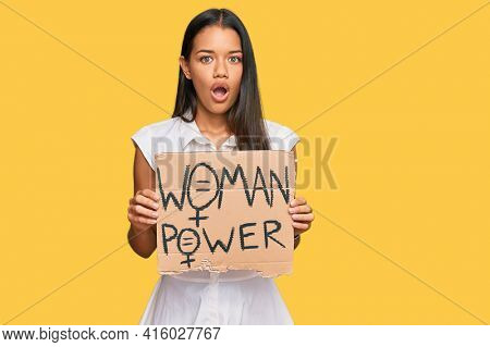Beautiful hispanic woman holding woman power banner scared and amazed with open mouth for surprise, disbelief face