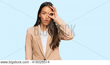 Beautiful hispanic woman wearing business jacket doing ok gesture shocked with surprised face, eye looking through fingers. unbelieving expression.