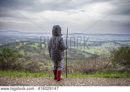 Child Boy Observing The Dehesa Landscape Outskirts Alburquerque, Extremadura, Spain. He Holds A Cane
