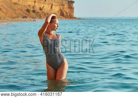 Young Pretty Woman Posing In Sea. Sexy Girl With Perfect Figure At Seashore. Summer Lifestyle And Su