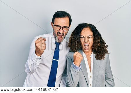 Middle age couple of hispanic woman and man wearing business office uniform angry and mad raising fist frustrated and furious while shouting with anger. rage and aggressive concept.