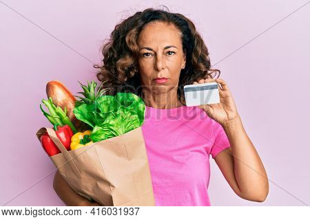 Middle age hispanic woman holding groceries and credit card skeptic and nervous, frowning upset because of problem. negative person.