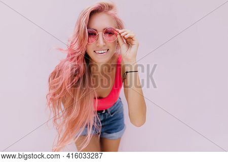 Interested Girl With Light-pink Hair Touching Her Sunglasses. Studio Shot Of Attractive Curly Woman