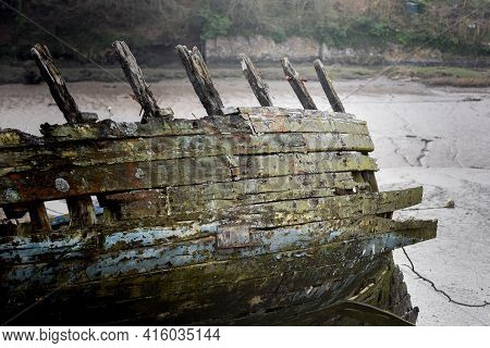 An Old Beached Wooden Boat Falling Apart And Decaying At Low Tide