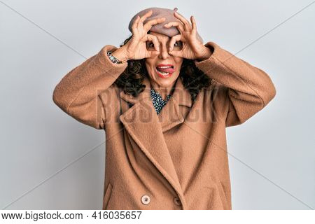 Middle age hispanic woman wearing french look with beret doing ok gesture like binoculars sticking tongue out, eyes looking through fingers. crazy expression.