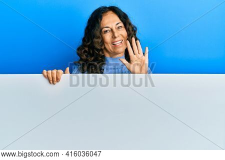 Middle age hispanic woman holding blank empty banner waiving saying hello happy and smiling, friendly welcome gesture