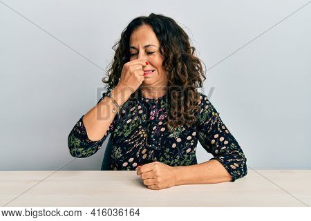 Beautiful middle age woman wearing casual clothes sitting on the table smelling something stinky and disgusting, intolerable smell, holding breath with fingers on nose. bad smell