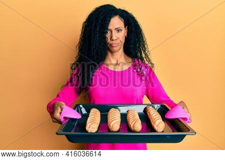 Middle age african american woman holding homemade bread skeptic and nervous, frowning upset because of problem. negative person.