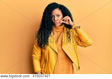 Middle age african american woman wearing wool winter sweater and leather jacket mouth and lips shut as zip with fingers. secret and silent, taboo talking