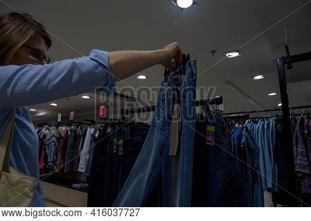 Strasbourg, France - July 29, 2017: Woman Shopping Inside Store For New Pair Of Jeans - Measuring In