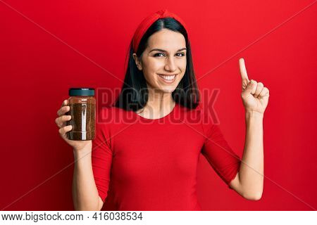 Young hispanic woman holding soluble coffee smiling with an idea or question pointing finger with happy face, number one