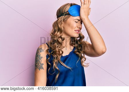 Young blonde girl wearing sleep mask and pyjama surprised with hand on head for mistake, remember error. forgot, bad memory concept.
