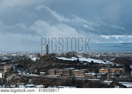 View Of Downtown Of Edinburgh In Winter With Historic Landmarks Under Dramatic Skies. Calton Hill In