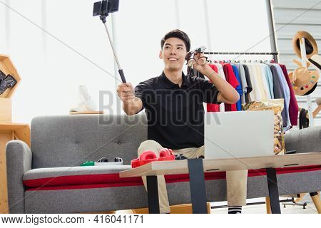 Online Blogger, A Young Asian Man, Uses A Smartphone To Record Live Video Vlog To Present Products V