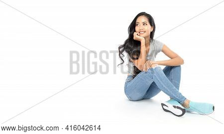 A Young Asian Woman Wore A Casual Dress Sit On The Floor. She Looks At The Copy Space. She Daydreams