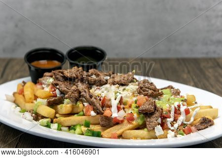Large Plate Of Asada French Fries Covered In Cheese Served With Dipping Sauce Will Tempt Everyone.
