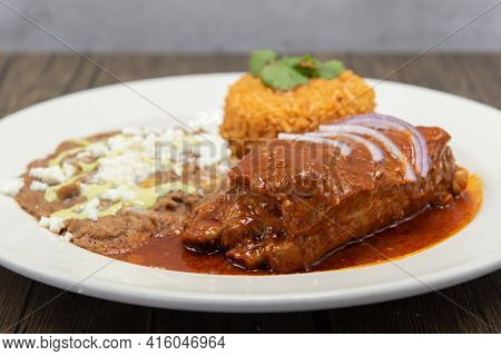 Large Slap Of Chile Colorado Entree Meat, Refried Beans, And Rice Drenched In The Red Sauce.