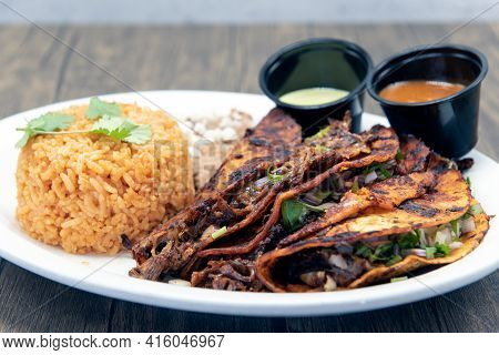 Threesome Of Red Birria Tacos Fried To Perfection Served On A Plate With Rice Mound And Refried Bean