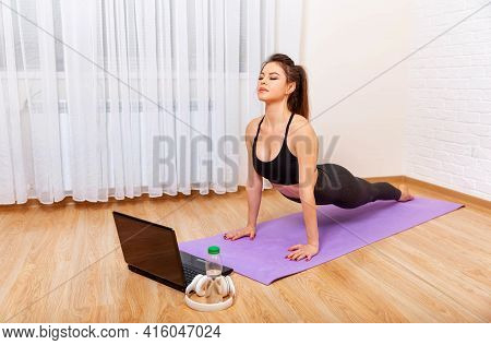 Achieving Sound Of Mind Through Yoga. Young Sporty Woman Practicing Yoga. Woman Exercising At Home I