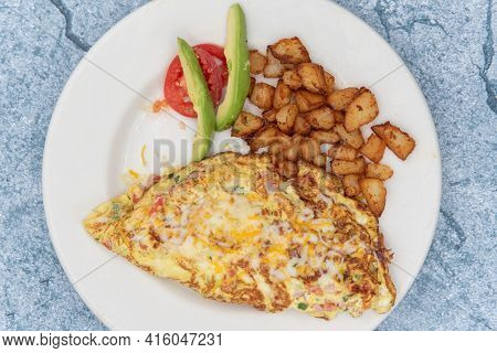 Overhead View Of Omelette Cooked To The Perfect Level Of Frimness Folded And Served With Cubed Break