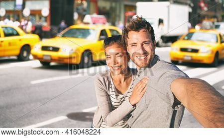New York travel selfie tourists couple taking photo on NYC city street summer holiday vacation with yellow taxi cabs in the background. Man and woman friends having fun.