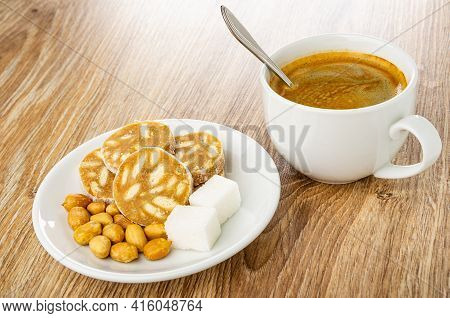 Slices Of Sweet Sausage, Fried Peanuts, Sugar Cubes In White Saucer, Spoon In Cup With Black Coffee