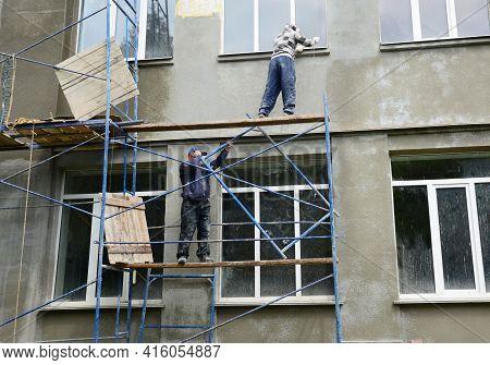 Kyiv, Ukraine - April, 05, 2021:  Building Contractors On Scaffolding Are Renovating, Plastering, Ap