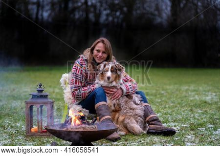 An Australian Shepherd Sits By The Campfire With His Owner In The Afternoon. Candles Burn In A Lante