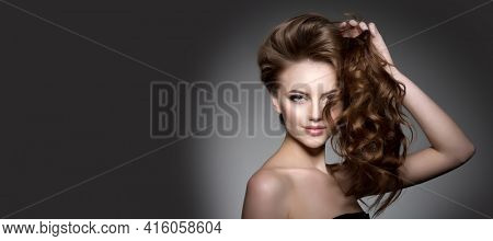 Model with long hair. Waves Curls Hairstyle. Salon. Updo. Fashion model with shiny hair. Woman with healthy hair girl with luxurious haircut.  Girl with hair volume.