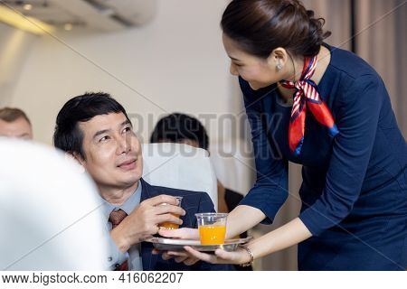 Passenger Have Orange Juice Served By An Air Hostess In Airplane, Flight Attendants Serve On Board