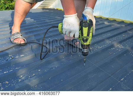 Roofing Construction: A Roofing Contractor Is Installing Metal Roofing Sheets, Metal Roof Tiles Driv