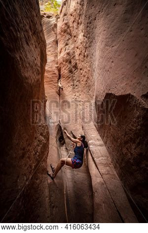 Diverse woman rock climbing in a beautiful slot canyon near Zion National Park. Using a rope to climb up out of a narrow slot canyon