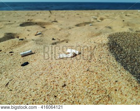 Old Cigarette Butts In The Yellow Sand On Beach With Water In Background As Toxic Plastic Pollution