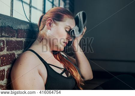 Woman wiping away her sweat with a gym towel