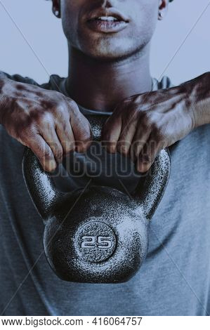 Muscular man weightlifting with a kettlebell