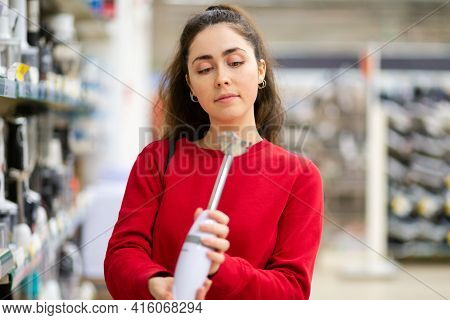 A Young Woman Chooses A Blender In A Home Appliance Store. Side View. The Concept Of Consumerism And