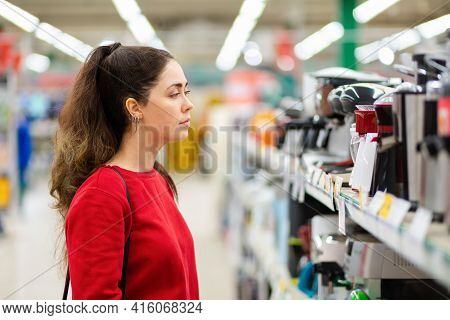 A Young Beautiful Woman Chooses Kitchen Gadgets In A Home Appliance Store. Side View. The Concept Of