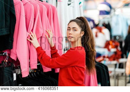 A Young Beautiful Caucasian Woman Choosing Clothes In A Store. Side View. The Concept Of Shopping An
