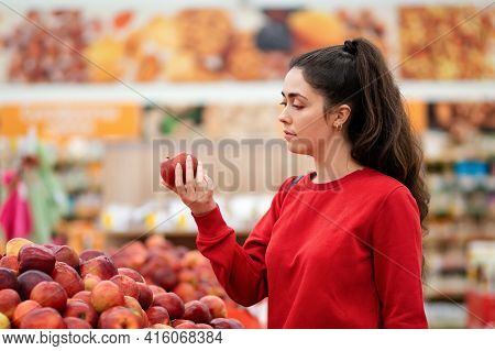 Shopping. Portrait Of A Young Caucasian Woman Choosing Apples In A Supermarket. The Concept Of Shopp